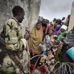 Flüchtlinge versuchen Einlass zur Lebensmittelverteilung zu bekommen. Das Gelände ist überfüllt. Bewaffnete Security Guards der Camp-Verwaltung riegeln die Zugänge ab.