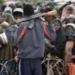 Flüchtlinge warten hinter ausgerolltem Springdraht auf die Verteilung der täglichen Reisrationen. Im Vordergrund ein Security Guard der Camp-Verwaltung.