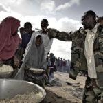 Auf dem Gelände der Lebensmittelverteilung sorgen Security Guards der Camp-Verwaltung unnachgiebig für einen schnellen Ablauf der Essensverteilung.