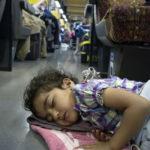 Auf dem Fussboden im Grossabteil des Nachtzuges schläft ein afghanisches Flüchtlingskind.