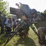 """Bei einem Pressetermin auf dem Truppenübungsplatz Hammelburg hocken die Fotografen um den kurdischen Major Abdullah, der die Panzerabwehrwaffe """"Milan"""" vorführt."""