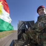 Ein Peschmerga auf einem Pickup unterwegs zur Front bei Mosul. Auf der Ladefläche des Pickups ist ein schweres Maschinengewehr montiert.