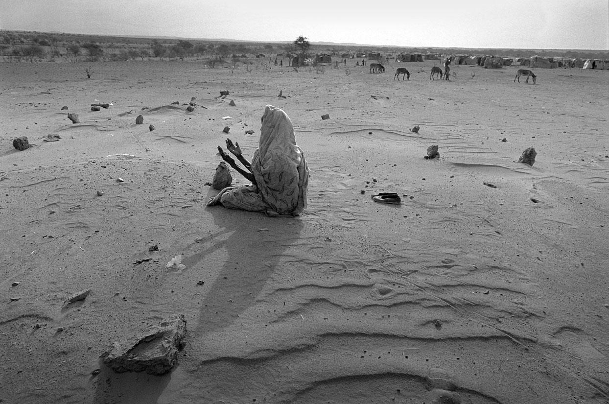 Eine Flüchtlingsfrau betet auf dem Gräberfeld des Flüchtlingscamps. Noch sterben täglich ca. 5 Flüchtlinge im Camp an den Strapazen der Flucht und an Unterernährung.