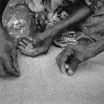 Nach der täglichen Ausgabe der nötigsten Nahrungsmittel an die Flüchtlingsfamilien sammeln Frauen die auf den Boden verbliebenen Getreidekörner auf.