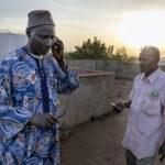 """Die Mitarbeiter der """"Association Malienne des Expulsés"""" Amadou Coulibaly (Person links) und Bassekou Siby erhalten einen Anruf vom Direktor des Busbahnhofes, der ihn über das Eintreffen von sechs Rückkehrern informiert, die jetzt auf dem Weg zum AME-Buero sind."""