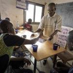 """Nach ihrer mühsamen Rückreise aus Nordafrika fanden sechs Migranten in der Hilfsorganisation """"AME"""" Zuflucht. Am Morgen nach ihrer Ankunft bekommen die Migranten vom AME-Mitarbeiter Bassekou Siby ein Frühstück."""