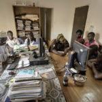 """Im Büro der Hilfsorganisation """"Association Malienne des Expulses"""" sind der AME-Mitarbeiter Amadou Coulibaly (1. Person v. links) und die ehrenamtliche AME-Mitarbeiterin Mariam Teme (4. Person v. links) mit der Registrierung der 6 Migranten beschäftigt."""