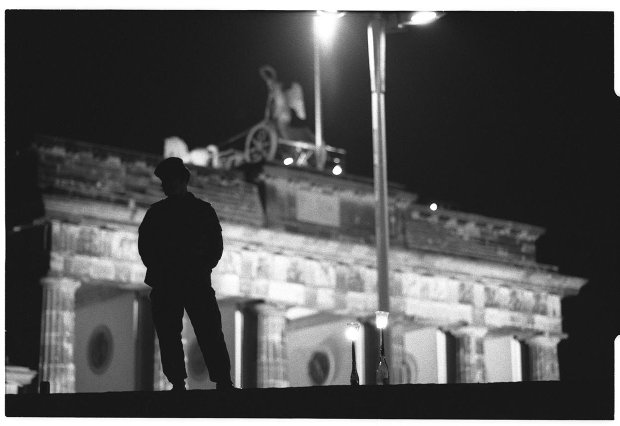 """Mit, auf der Mauer patrouillierenden DDR-Grenzsoldaten versucht das """"Grenzkommandos Mitte"""" das aufzuhalten, was nicht mehr aufzuhalten ist."""